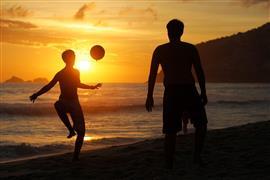 شباب برازيليون يلعبون الكرة على شاطئ