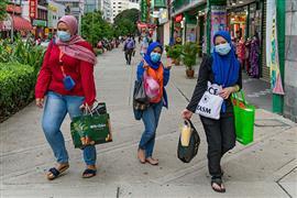 الماليزيون يشترون ملابس العيد بـالكمامات