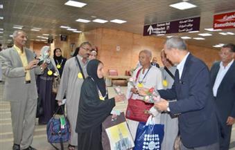 بالصور.. محافظ قنا يستقبل حجاج بيت الله بالورد بمطار الأقصر الدولي