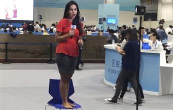 """بالفيديو.. طرائف المركز الصحفي.. مذيعة برازيلية تقف حافية على كرسي لتقديم """"قمة العشرين"""" في الصين"""