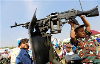 أطفال تايلاند يلعبون بالأسلحة ويلتقطون الصور مع رئيس الوزراء في يومهم الوطني| صور