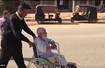 شرطي يساعد مسنا للوصول إلى لجنته الانتخابية في مدينة بدر