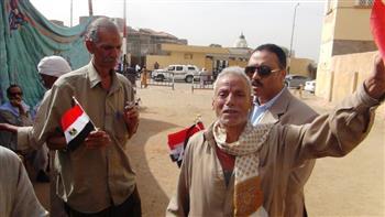 وكيل مباحث مديرية أمن أسوان يوزع أعلام مصر على الناخبين | صور
