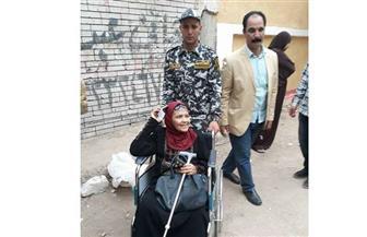 قوات الأمن تنقل مسنة على كرسي متحرك للتصويت بلجنتها الانتخابية بحي المعصرة   صور