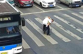 شرطي صيني يحمل رجلا مسنا على ظهره ويعبر به الشارع | فيديو