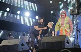 تامر حسنى يحتفل بشفاء طفل من السرطان على خشبة المسرح | صور