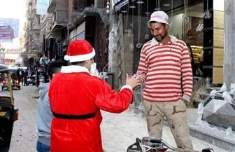 رغم سوء الطقس.. شاب يرتدي زي بابا نويل ويوزع هدايا مجانية على المواطنين بالغربية | صور