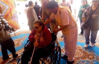 رجال الشرطة يساعدون سيدة مسنة من ذوي الاحتياجات الخاصة على الإدلاء بصوتها في أكتوبر