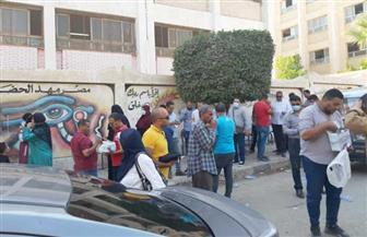 توزيع كمامات طبية على الناخبين بمدرسة محمود عمر بحدائق الأهرام