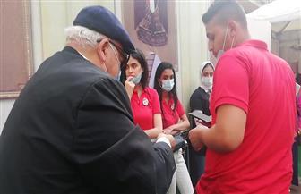 متطوع يساعد مسنا للإدلاء بصوته بلجان الجامعة العمالية | صور وفيديو