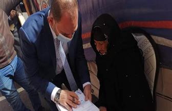 رئيس لجنة يساعد سيدة مسنة تجاوز عمرها 90 عاما  للإدلاء بصوتها