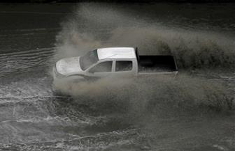 عروسان يتغلبان على غرق الشوارع بالجرار لتفادي مياه الأمطار| فيديو