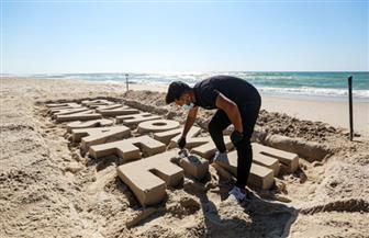 فنانون غزاويون ينحتون لوحات على الرمال بعنوان «ابقوا في المنزل» | صور
