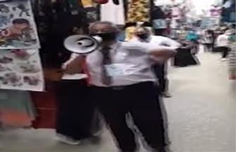 مواطن يستخدم مكبر صوت ليحذر المواطنين من خطورة التجمعات | فيديو