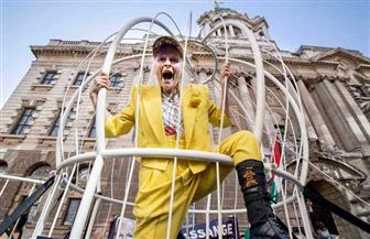 مصممة أزياء شهيرة تدعو إلى إطلاق سراح جوليان أسانج من داخل قفص طيور ضخم في لندن