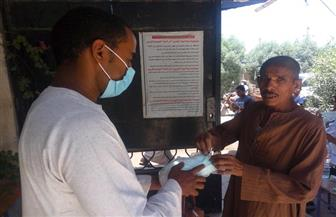 شباب قنا يوزع كمامات طبية ويساعد كبار السن في لجان انتخابات مجلس الشيوخ | صور