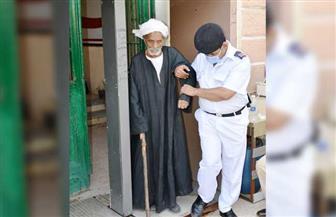رجل شرطة يساعد مسنا للوصول إلي لجنة التصويت بأسوان | صور
